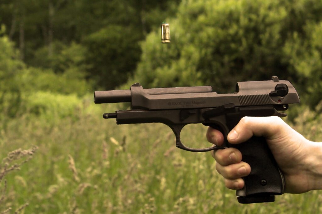A pistol being shot with a flying bullet
