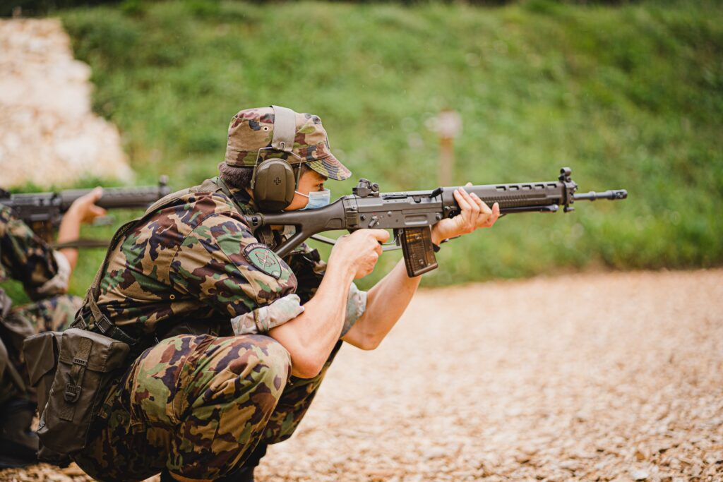 A person wearing soldier equipment while aiming a gun