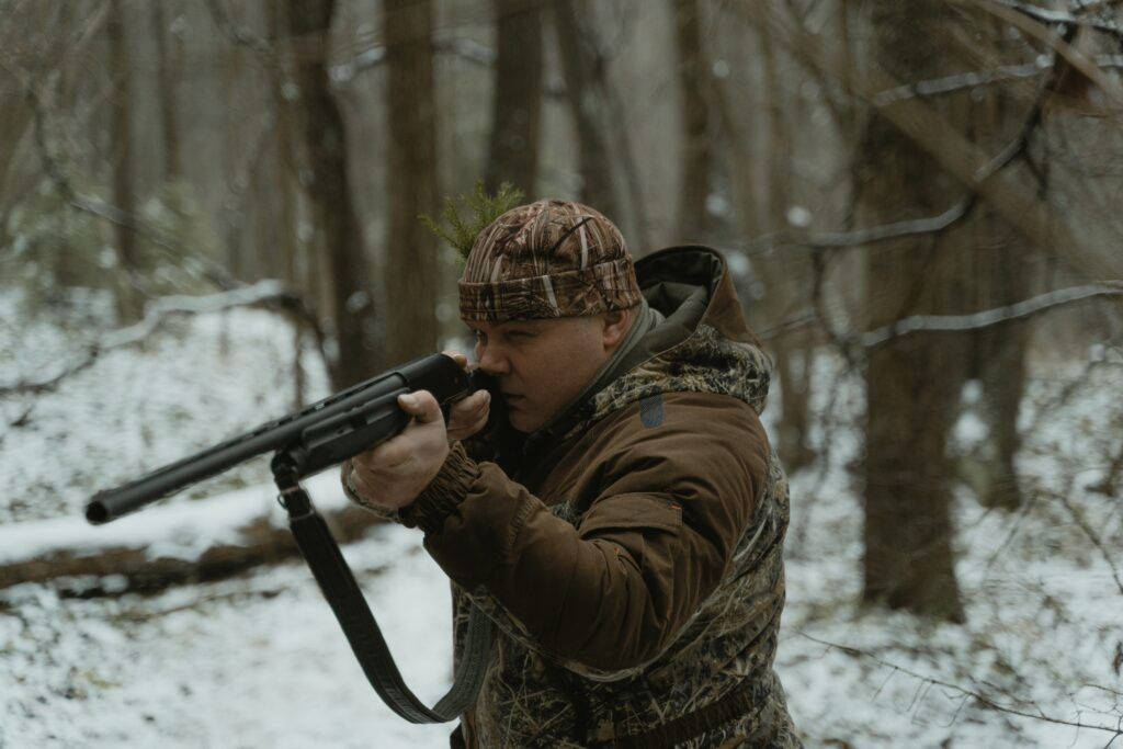 A person wearing a brown camo while aiming with a long gun
