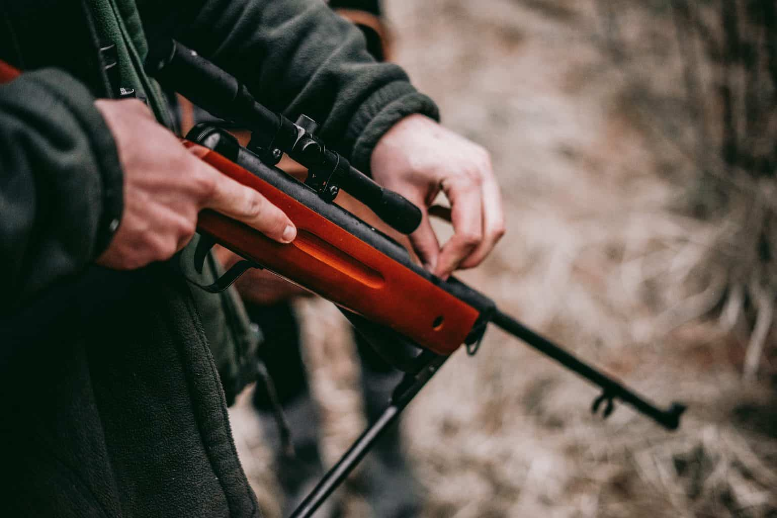 A person holding down a red sniper hunting rifle