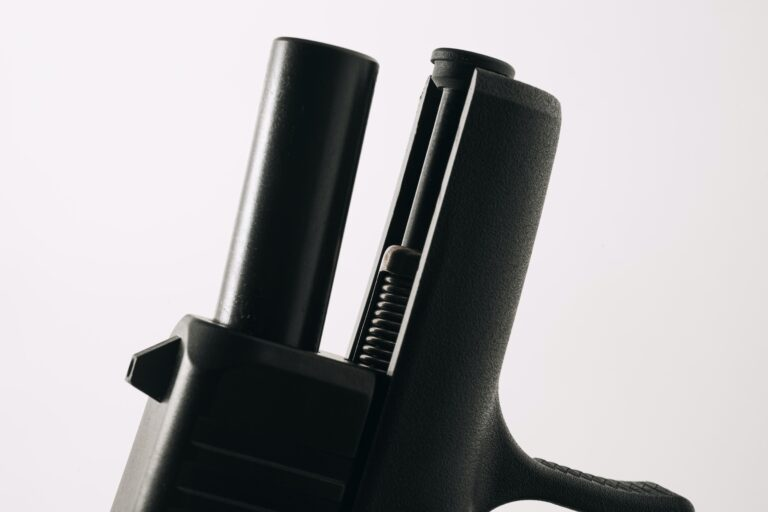 A pistol with exposed barrel and guide rod