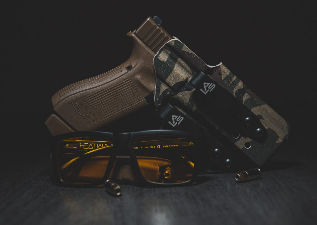 A brown handgun with protective glasses