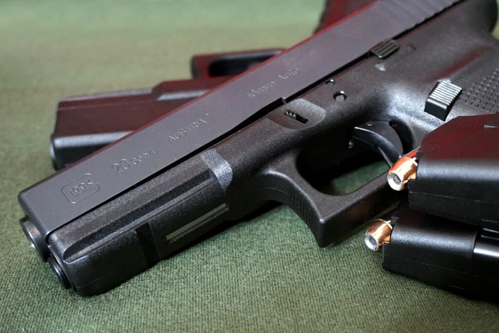 A glock with ejected magazine on a green table