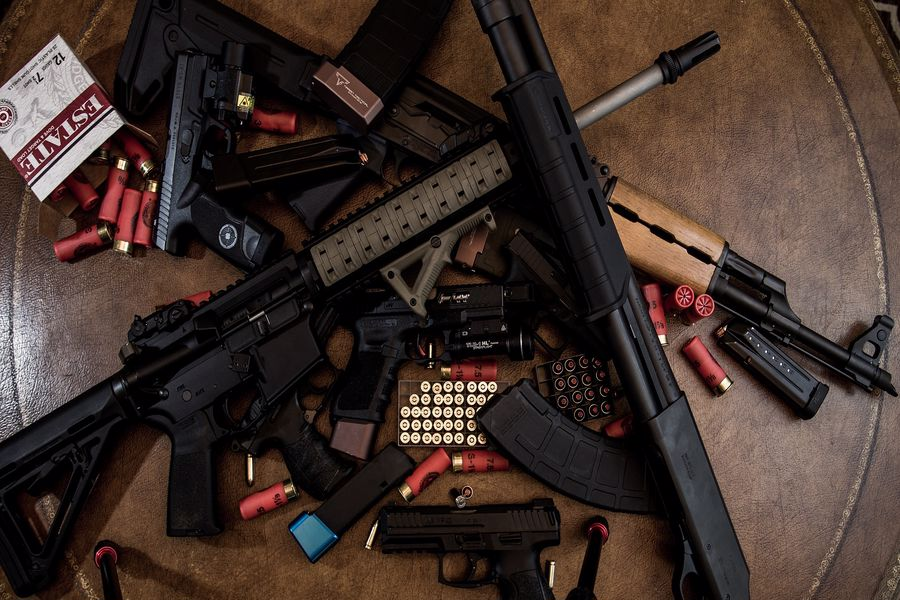 Various rifles and gun accessories in a table