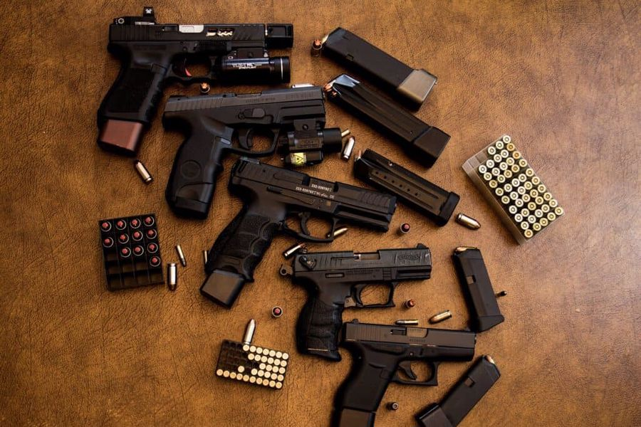 Various kinds of handguns and multiple bullets in boxes laid on a table