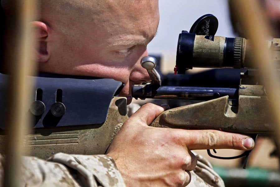 Man holding a rifle while looking at his scope
