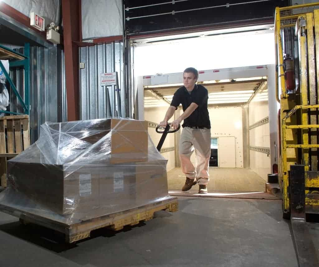 Man moving heavy boxes with a wood pallet