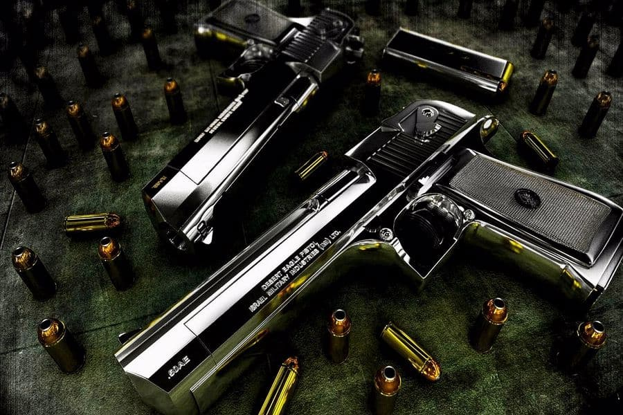Two handguns with bullets around them