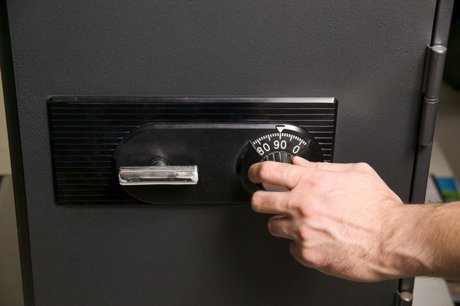 Hand trying to open a combination lock