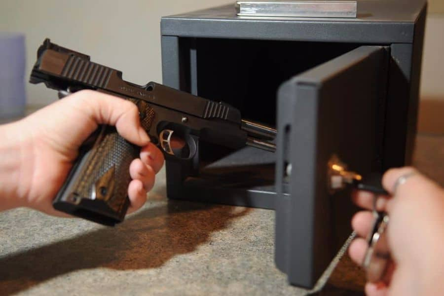 Person trying to fit a gun inside a safe