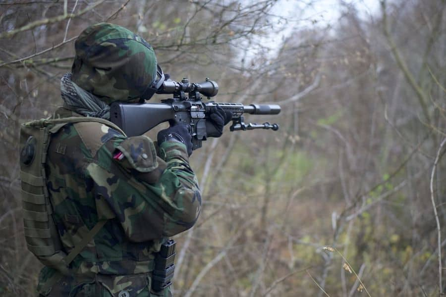 Man looking at his rifle scope
